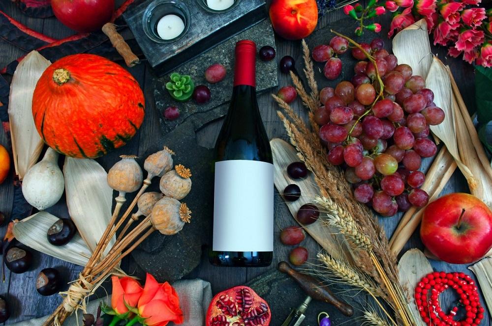 bottiglia di Novello su tavolo autunnale con uva, zucche e melograne